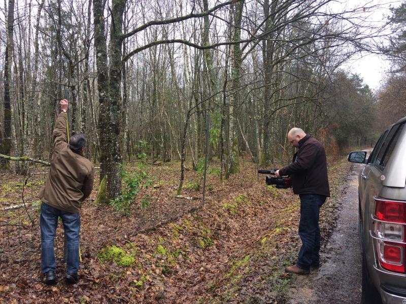 Raymond mesurant la hauteur d'un grillage devant la caméra de David